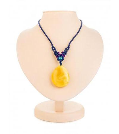 Stylish pendant made of solid amber on a cord in Asian style
