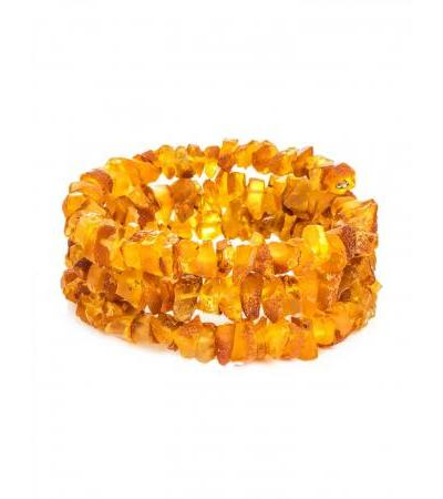 Healing bracelet made of unpolished amber on a string in three turns