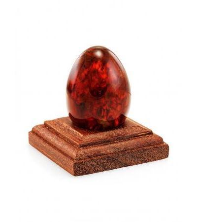 Easter egg made of molded cognac-red amber on a wooden stand