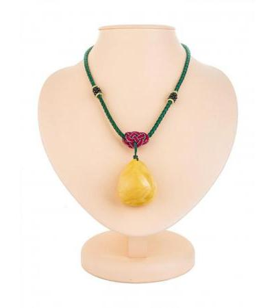 Necklace on a string with a volumetric pendant made of solid honey amber
